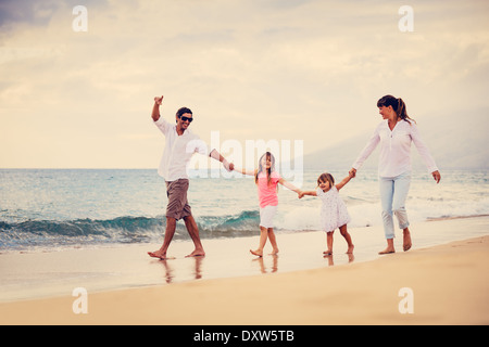 Happy Young Family have Fun Walking on Beach at Sunset - Stock Photo