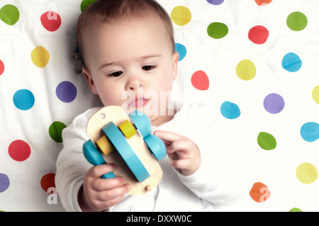 One year old baby boy on spotty blanket playing with wooden train - Stock Photo