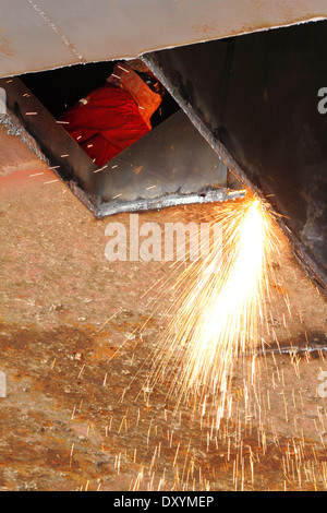 Sparks fly as steel is cut from an old barge by an oxy acetylene torch at a shipyard in Malaysia. - Stock Photo