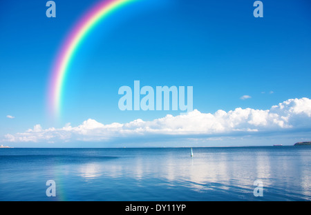 Rainbow on blue sky over endless water - Stock Photo