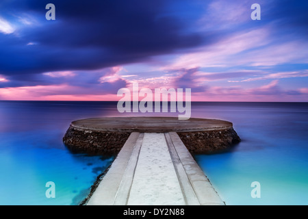 Beautiful pier in sunset, dramatic purple and blue cloudy sky, place for romantic dinner, luxury resort on Maldives - Stockfoto