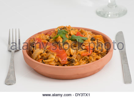 Dish of a delicious paella using the Cuban cuisine way or style. Served in a pottery plate and over a white background - Stock Photo