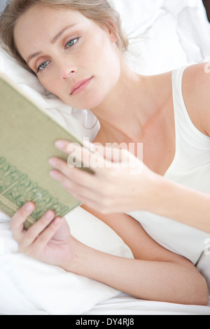 Young Woman Reading in Bed - Stock Photo