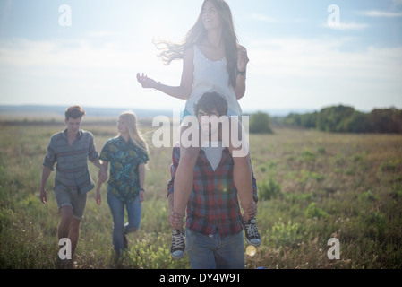 Friends walking in field, man carrying woman on shoulders - Stock Photo
