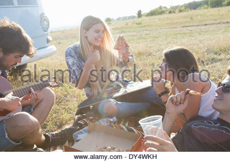 Four friends sharing pizza, man playing guitar - Stock Photo