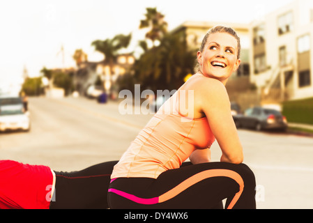 Two runners taking a break on a city hill - Stock Photo