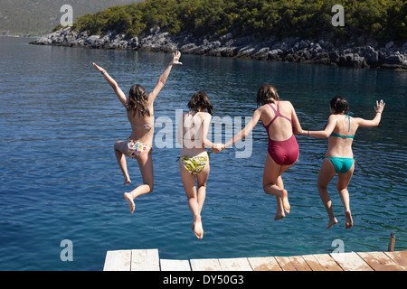Four girls jumping from pier into the sea - Stock Photo
