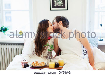 Young couple kissing, having breakfast in bed - Stock Photo