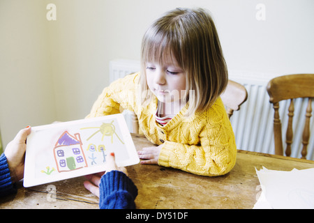 Young girl and mother at kitchen looking at drawing - Stock Photo