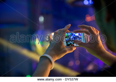Man taking photograph in nightclub with cellular phone - Stock Photo