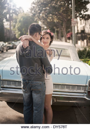 Couple embracing next to convertible car - Stock Photo