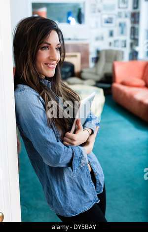 Young woman in sitting room holding digital tablet - Stock Photo