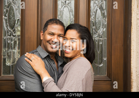 Portrait of happy mid adult couple at front door - Stock Photo
