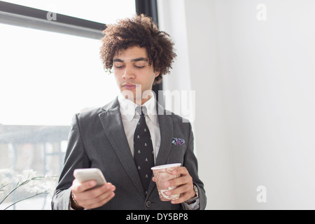 Young man using cell phone with coffee - Stock Photo