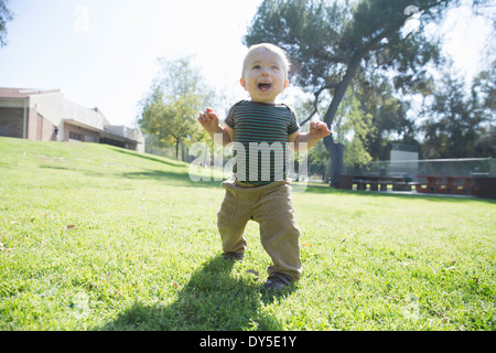 Baby boy learning to walk on grass - Stock Photo