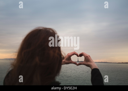 Young woman making heart shape around statue of liberty, New York, USA - Stock Photo