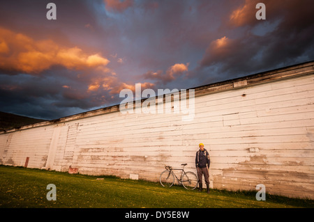 Young man standing next to white wall with his bicycle - Stock Photo