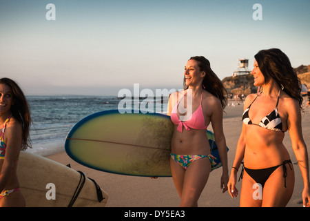 Surfers carrying surf boards, walking along beach - Stock Photo