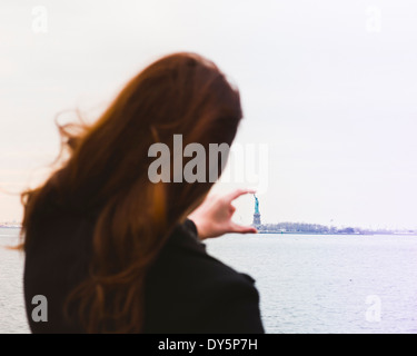 Young woman aligning fingers with statue of liberty, New York, USA - Stock Photo