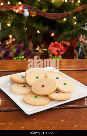 Plate of shortbread cookies in front of the Christmas tree - Stock Photo
