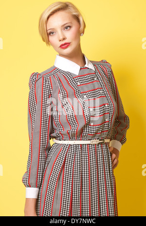 Short blond hair woman,Caucasian female model posing in studio against yellow background, a vintage fashion concept - Stock Photo