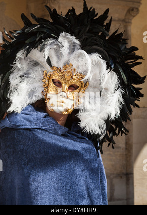 Close up of man in historic gold mask and feathered headgear at the carnival in Venice - Stockfoto