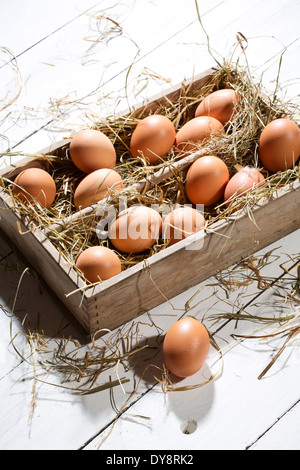 Wooden box of brown eggs and hay on white wooden table - Stock Photo
