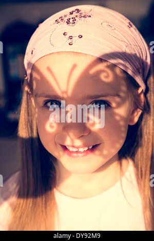 Portrait of smiling little girl with butterfly shaped shadow on her face - Stock Photo