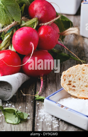 Fresh wet radishes with sea salt and bread over old wooden table - Stock Photo