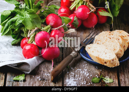 Fresh wet radishes with vintage fork, sea salt and bread over old wooden table - Stock Photo