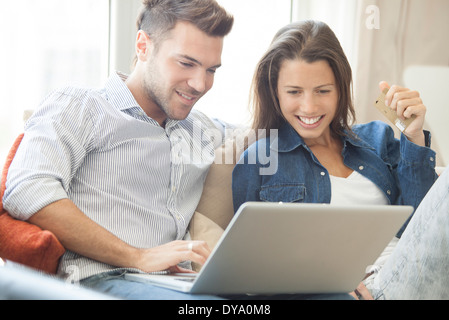 Couple at home shopping online together - Stock Photo