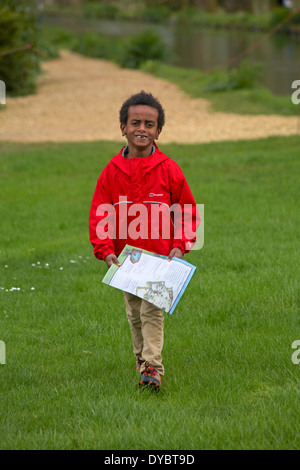 smiling young boy with missing front teeth walking and carrying Easter Egg hunt map - Stock Photo