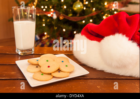 Plate of shortbread cookies with a glass of milk and Santa hat - Stock Photo