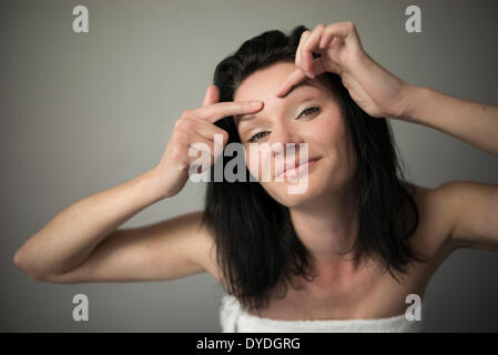 A beautiful cheeky girl squeezing her brow. - Stock Photo