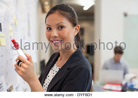 smiling Businesswoman front whiteboard in office - Stock Photo