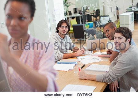 Smiling woman writing on whiteboard in conference room - Stock Photo