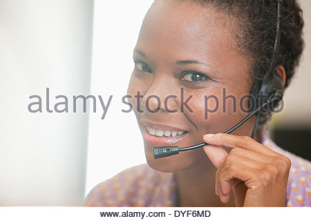 Close up of happy businesswoman using headset - Stock Photo