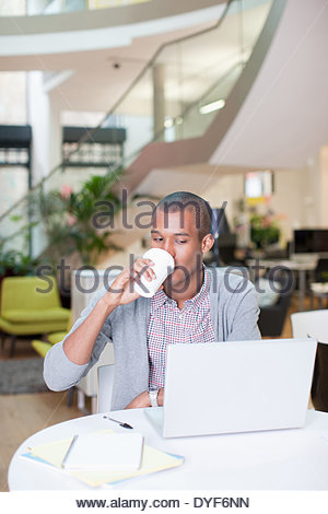 Portrait confident businessman looking  laptop drinking coffee in office - Stock Photo