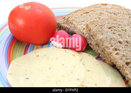 Scheiben von Roggenbrot, Tomaten, Käse, Rettich auf einem farbigen Teller - Stockfoto