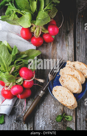Fresh wet radishes with vintage fork, sea salt and bread over old wooden table. Top view - Stock Photo