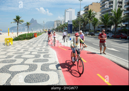 RIO DE JANEIRO, BRAZIL - APRIL 1, 2014: Cyclist rides along red boardwalk bike path on Avenida Vieira Souto in Ipanema. - Stockfoto