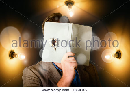 Business man covertly holding book with spy hole searching, monitoring and tracking in a depiction of market research - Stock Photo