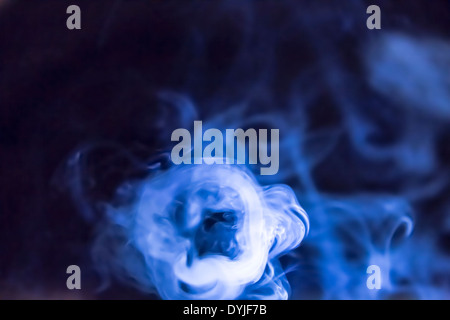Smoke from a cigarette lit by a powerful torch to highlight the patterns. - Stock Photo