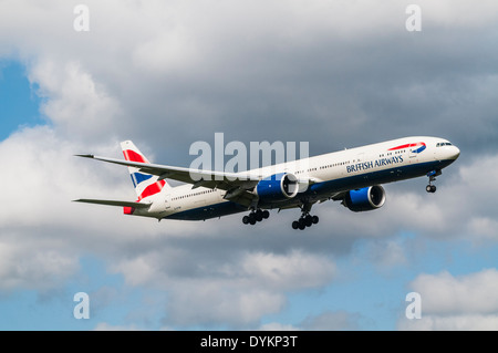 Side view of a British Airways Boeing 777 aircraft on approach to land with landing gear down - Stock Photo