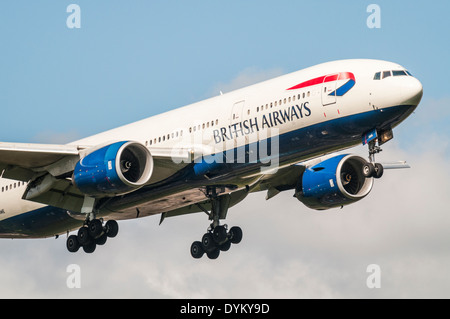 Front of a British Airways Boeing 777 aircraft on approach to land with landing gear down - Stock Photo