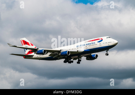 Side view of a British Airways Boeing 747 Jumbojet aircraft on approach to land with landing gear down - Stock Photo