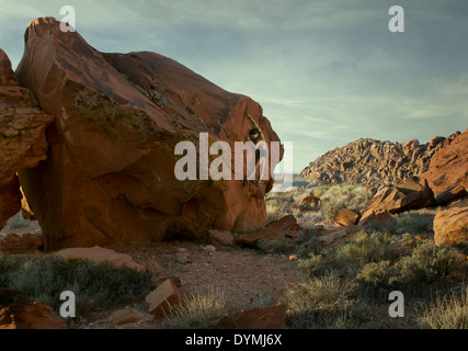 A female climber boulders a golden orange sandstone boulder face in the setting sun. - Stock Photo