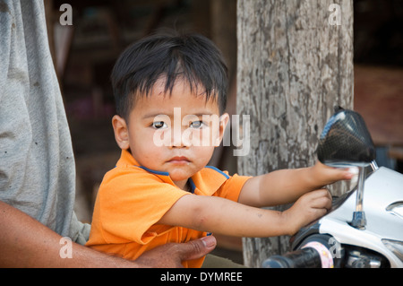 Horizontal portrait of an attractive young boy on the front of a motorbike in Laos. - Stock Photo