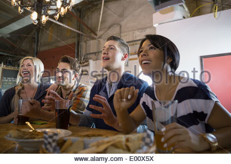 Friends watching sports on TV at brewery - Stock Photo