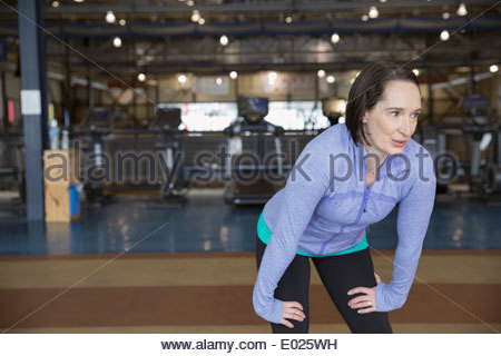 Woman resting hands on knees at gym - Stock Photo